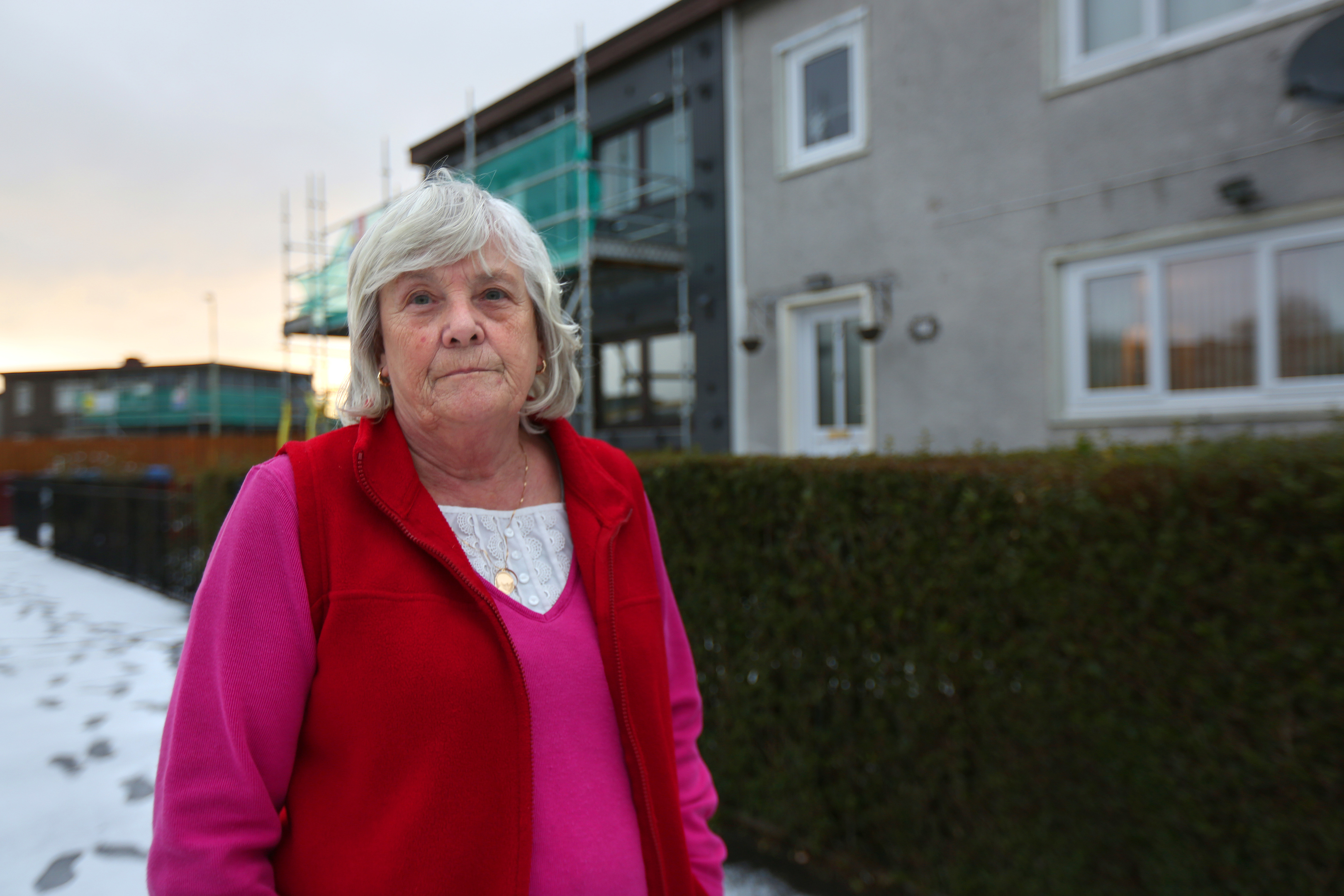 Margaret Davidson outside her property on Dryburgh Street. The house to the left of hers is currently undergoing work to install the external wall insulation, which she is not eligible for according to the council.