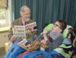 Pictured at Rachel House, poet Robin Bell reads a Beano comic to Brooklyn age 13