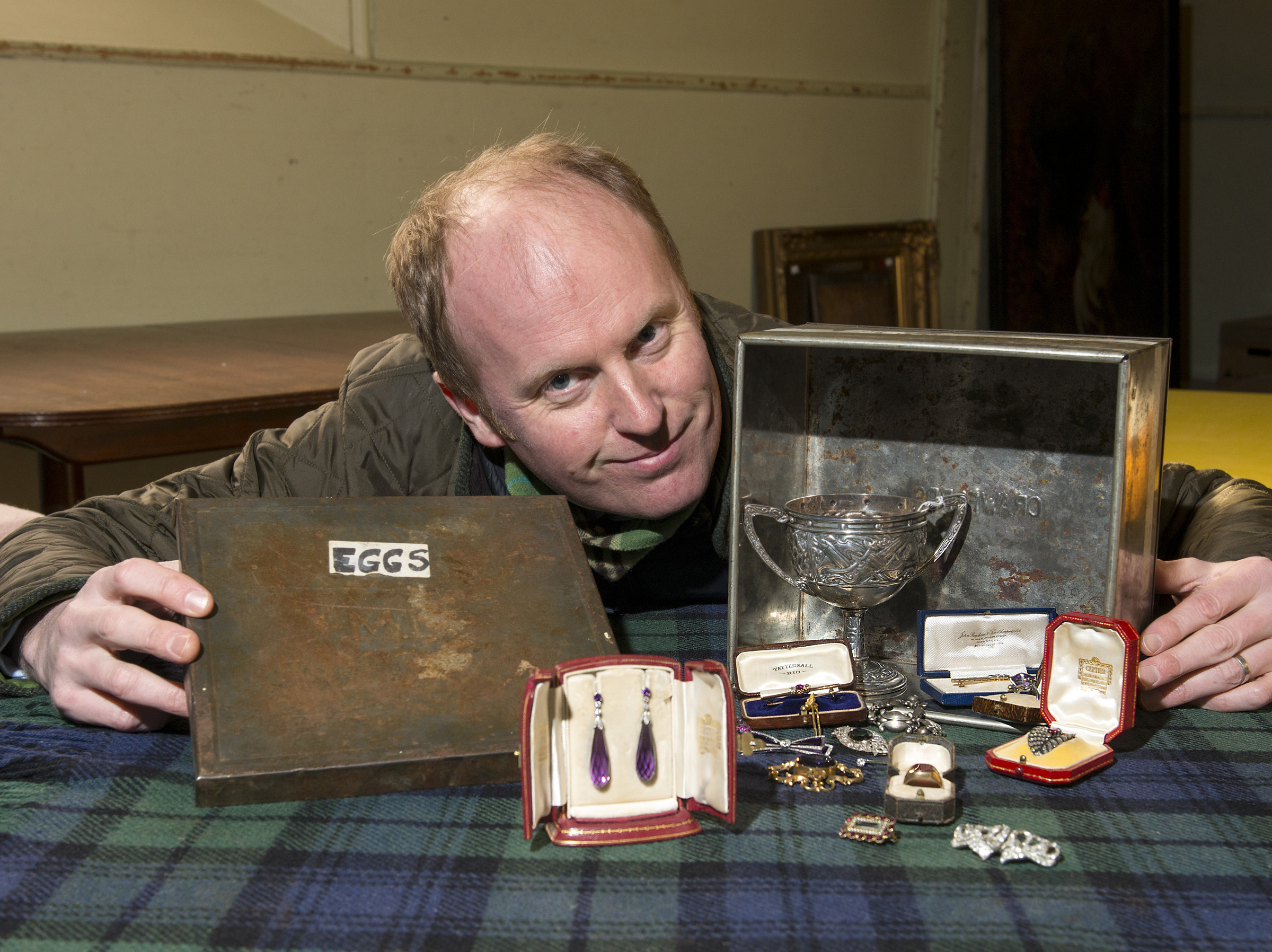 Auctioneer Nick Burns with the old tin box and Cartier items.