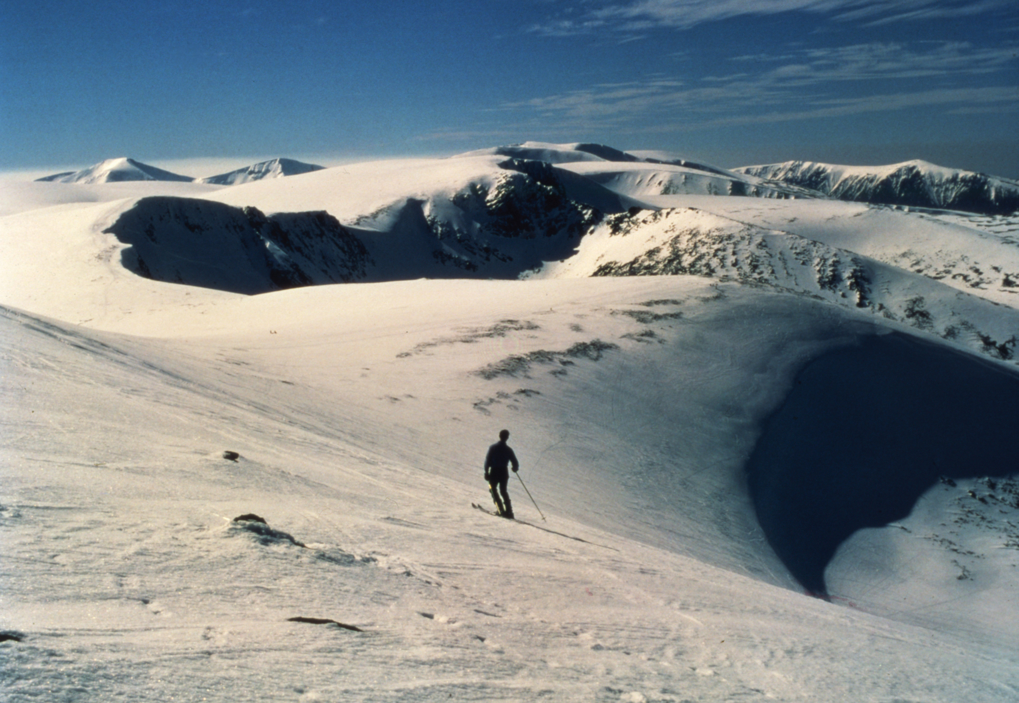 A lone skier surveys the surrounding peaks from Coire Cas in the Cairngorms.