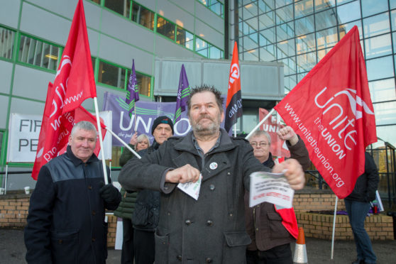 Tam Kirby rips up a booklet of promises made by Fife councillors at a trade union led protest before Fife Council's budget meeting in Glenrothes.