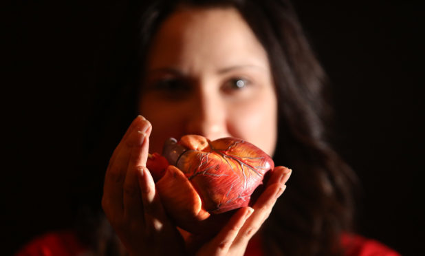 Claire Cunningham, a mortuary technician at Dundee University with a model of a heart.
