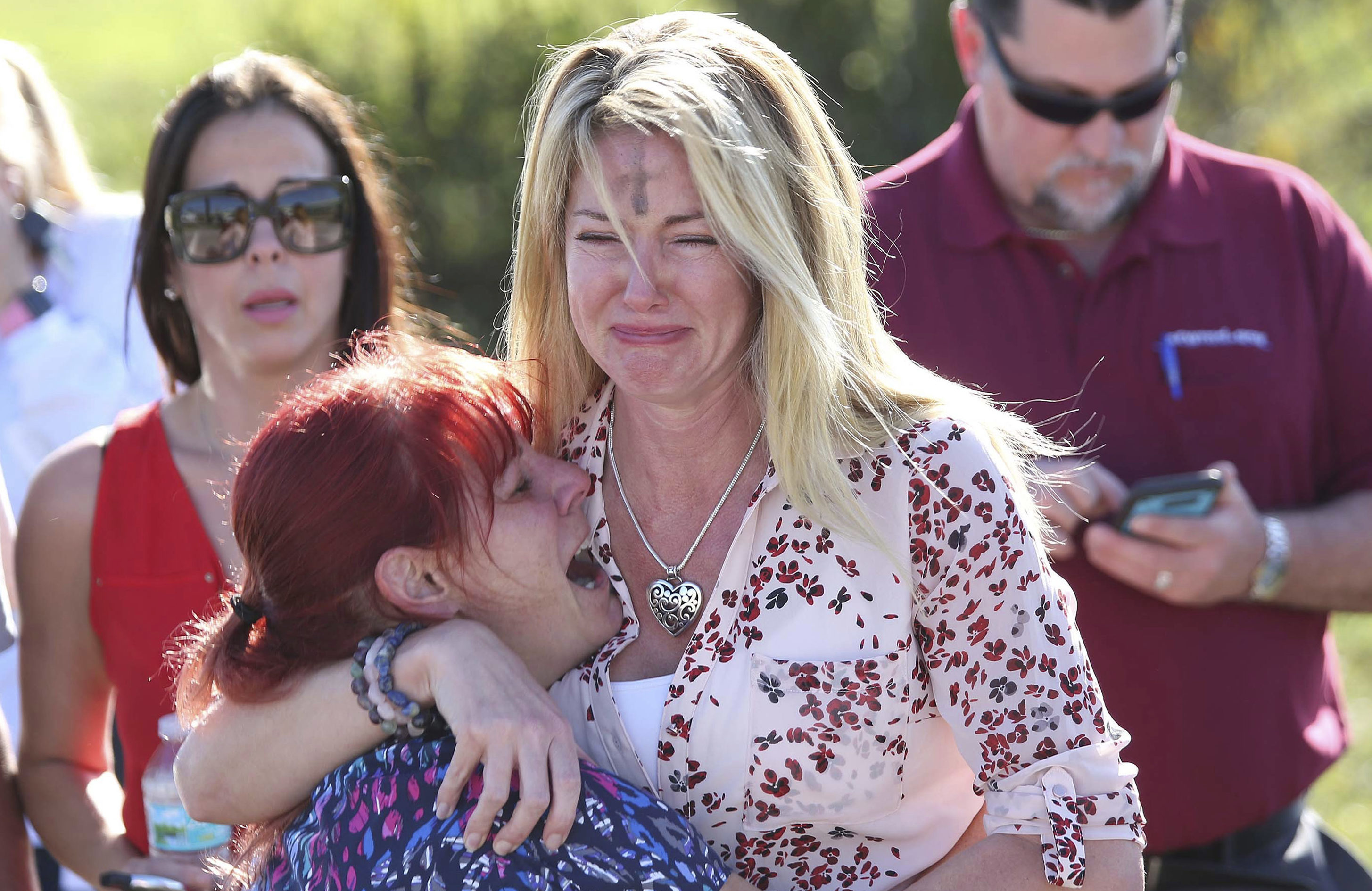 Parents wait for news after a reports of a shooting at Marjory Stoneman Douglas High School in Parkland, Fla., on Wednesday, February 14