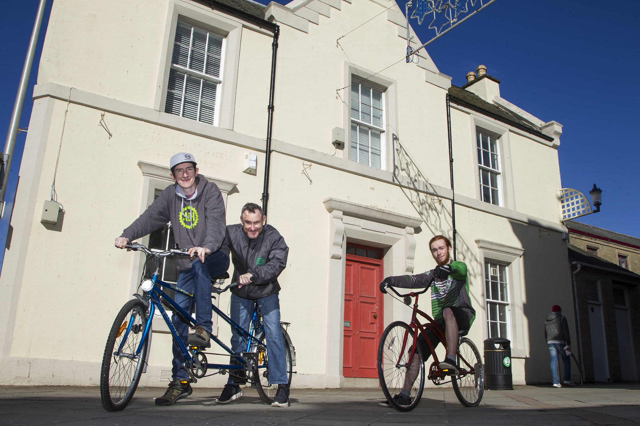 Project Director Scott Francis(left) on a tandem with volunteer Jeff Williams and community mechanic Calum Watson (right) outside the new premises