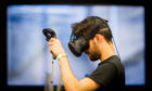 An Abertay University games student plays a virtual reality game.
