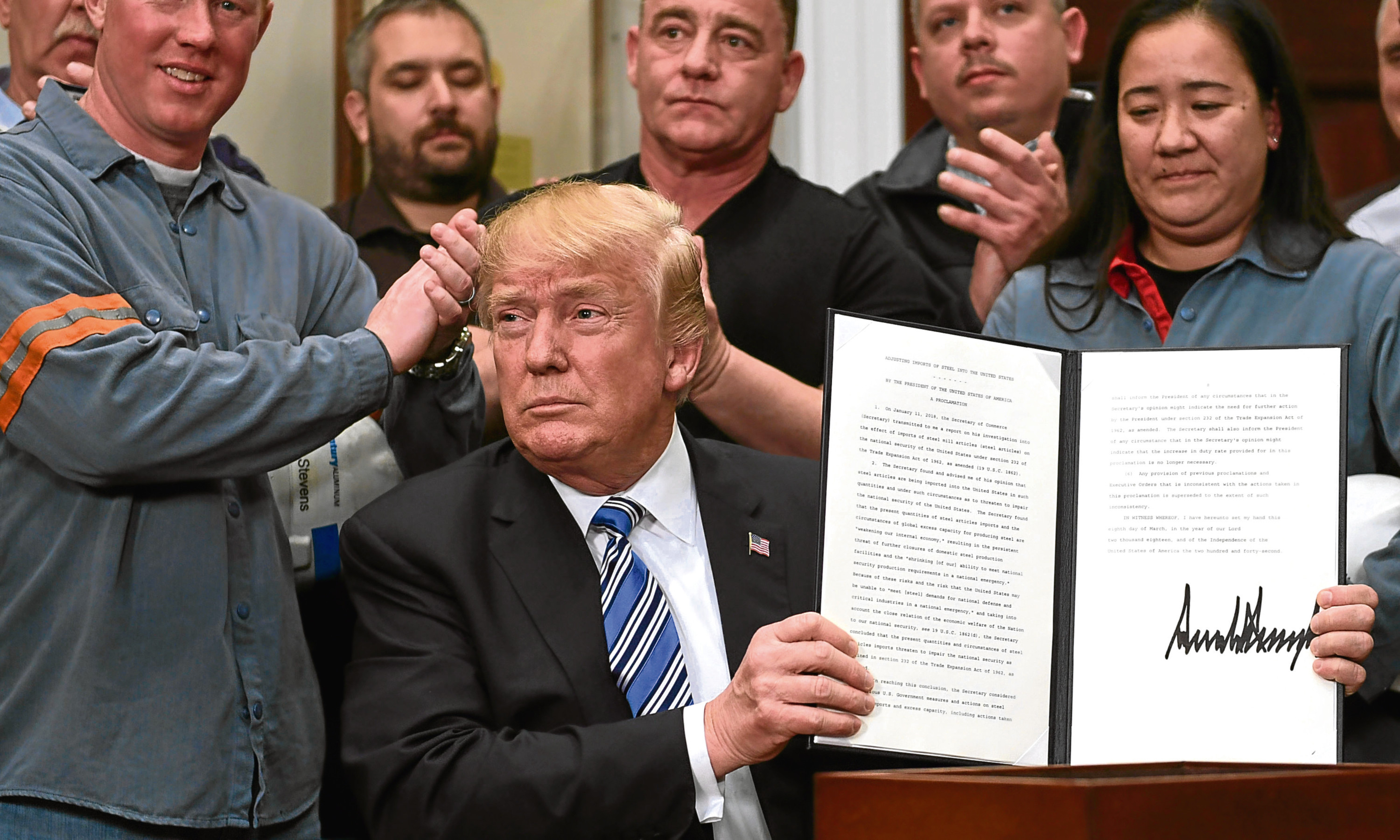 US President Donald Trump signs into law new tariffs on the import into the US of steel and aluminum.