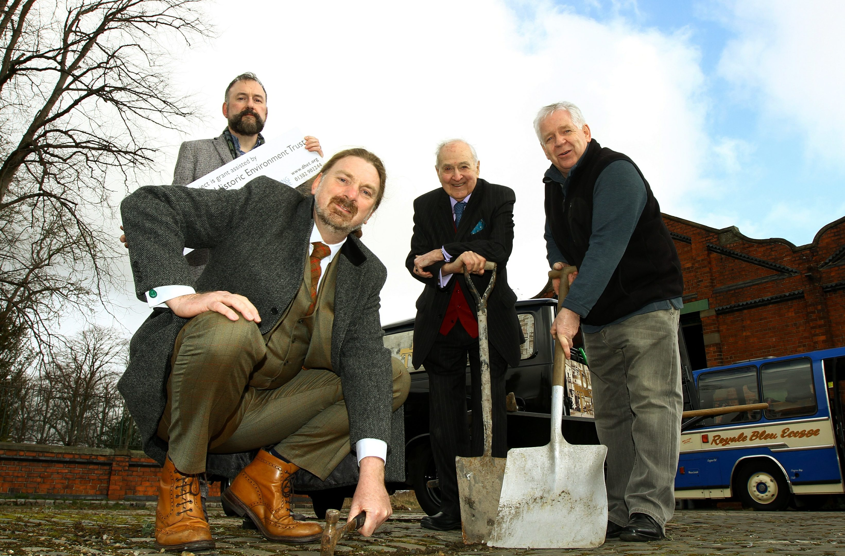 Chris Law MP lending a hand at the launch of the first phase of works on the former Maryfield Tram Depot, with L/R, Adam Swan - Director Dundee Historic Environment Trust, Norman Robertson - Trustee of the Dundee Museum of Transport and Jim McDonnell - Chairman.