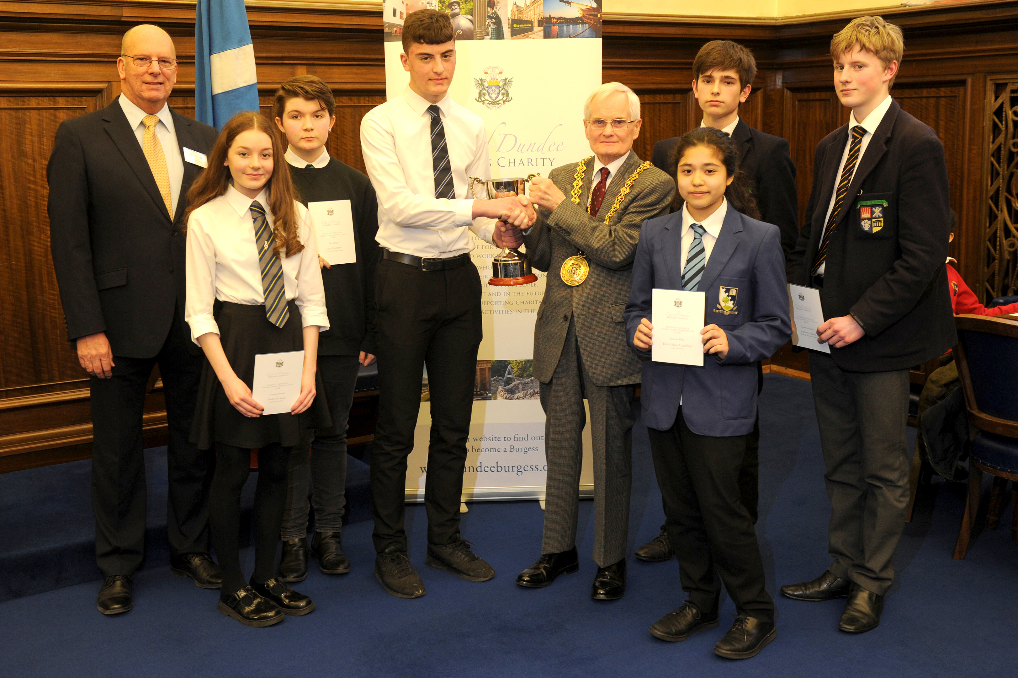 Lewis Neilson receives the trophy from Lord Provost Ian Borthwick and City of Dundee Burgess Charity chairman Brian McLeod (left). Also pictured are pupils Molly Dickson of Morgan Academy (worth of mention), Lucy Johnston of St Paul's RC Academy (third place), Emily Crawford of Grove Academy (second place) and Daniel Hamilton and Anthony Mills of Dundee High School (both worthy of mention).