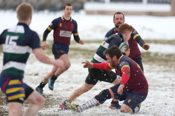 Medics' Michael Finnerty goes through the snow and the Panmure defence during Saturday's BT Midlands Bowl Final at Forthill.