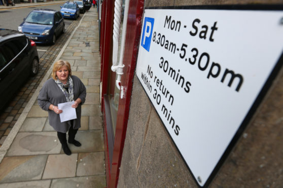 Jill Scott in Brechin High Street, with her petition against proposed parking charges.