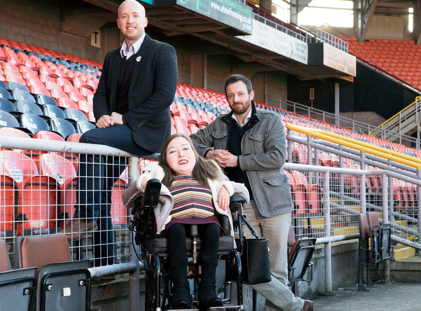 Richard Meiklejohn and Michael Leeland, of OOVIRT and wheelchair user Clair D'All at Tannadice park.