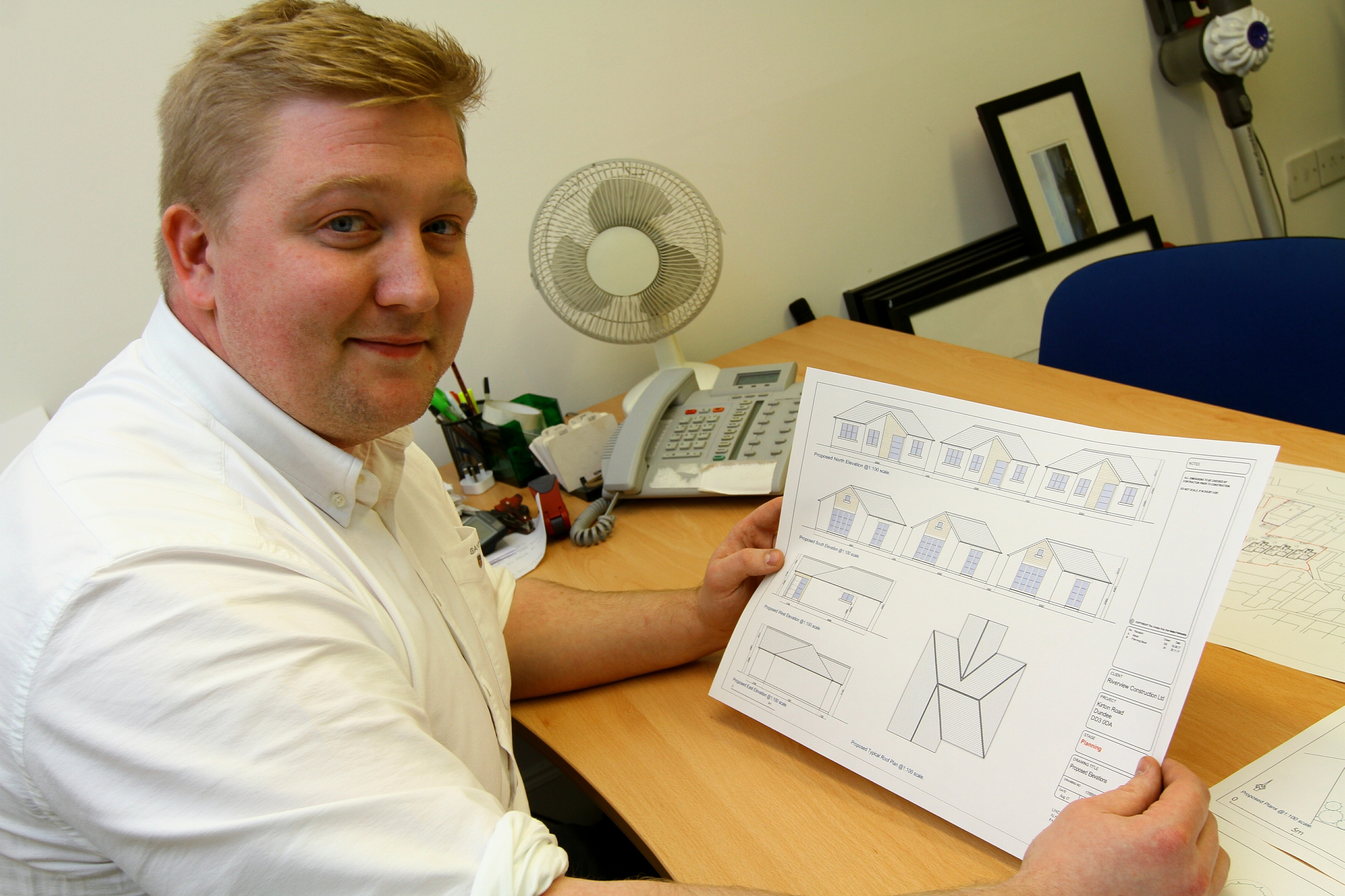 Owen Dyer with drawings of the proposed houses.