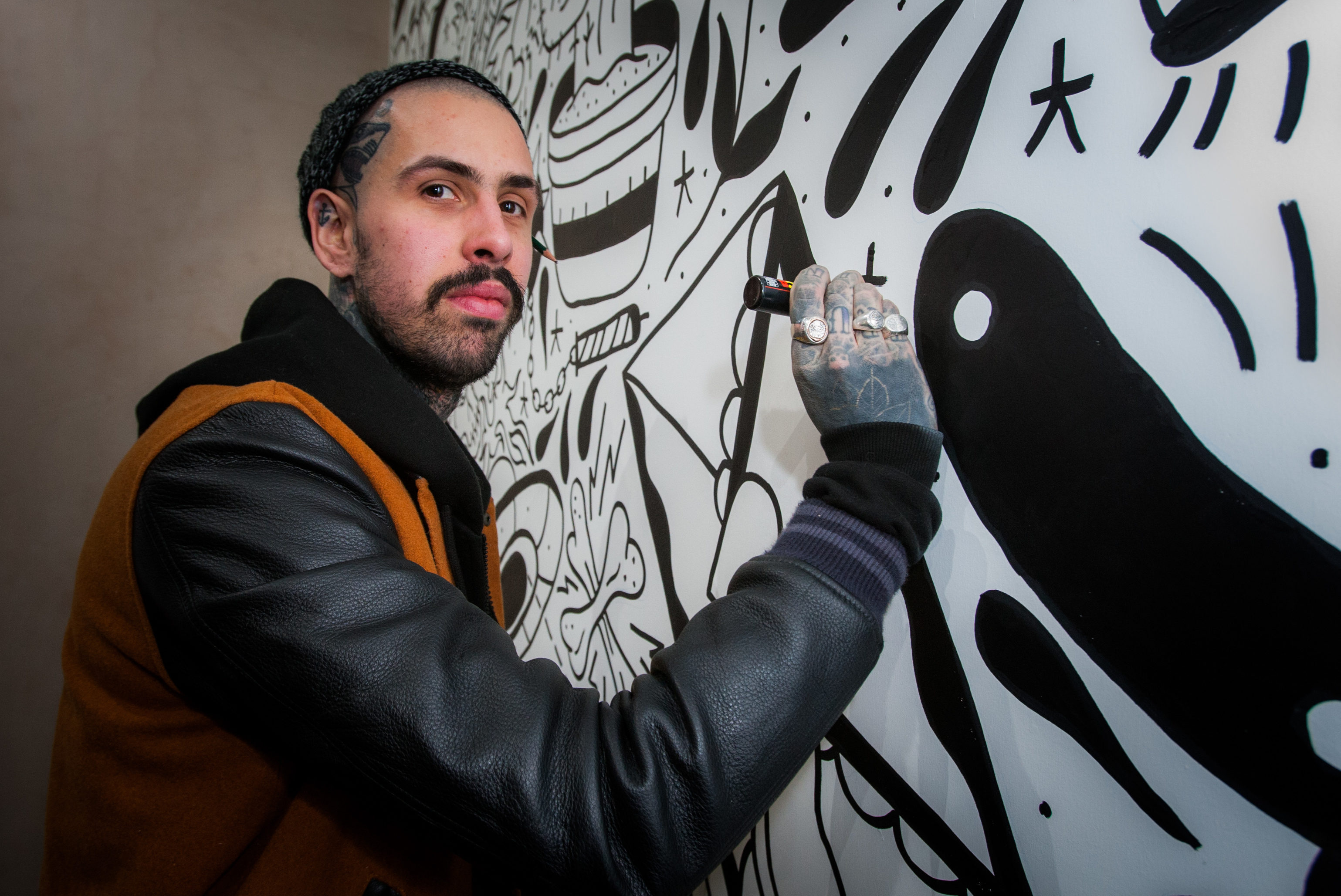 Richard Davies working on wall murals at his recently opened coffee shop, Daily Grind