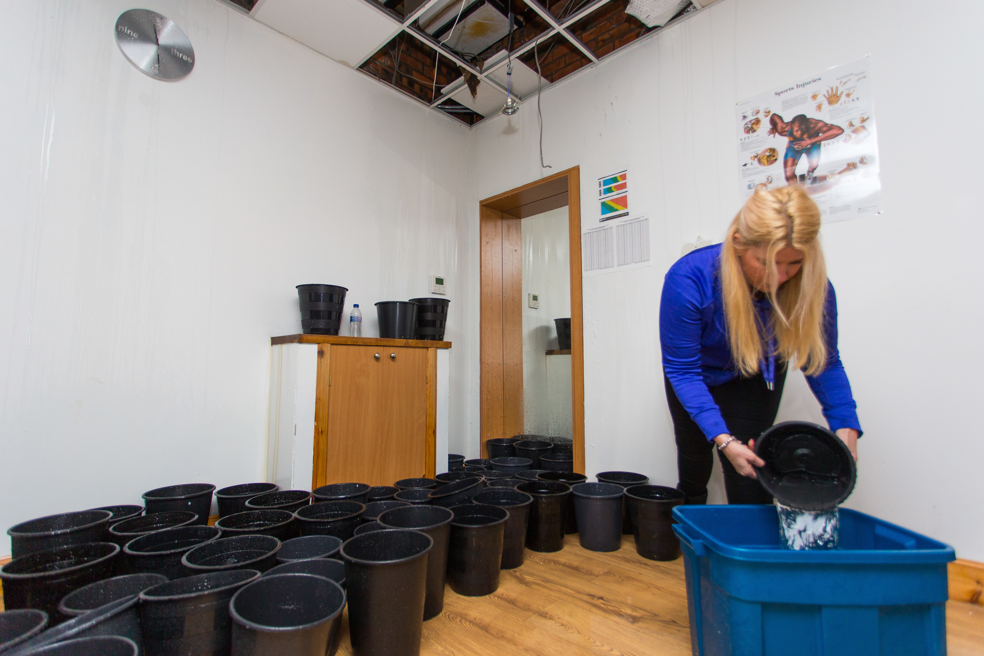 Lorna Wallace emptying buckets as the water continues to enter the roof.