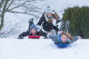 Children having fun sledging at Riverside Park in Glenrothes. The smiles will be bigger when they learn school is off until Monday.