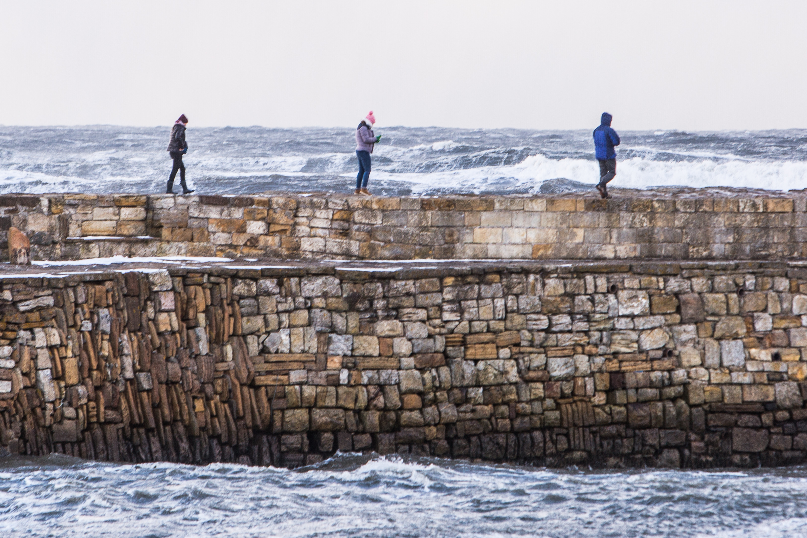 St Andrews has a dramatic backdrop of turbulent sea as these students find out, some taking unecessary risks by climbing the top wall.
