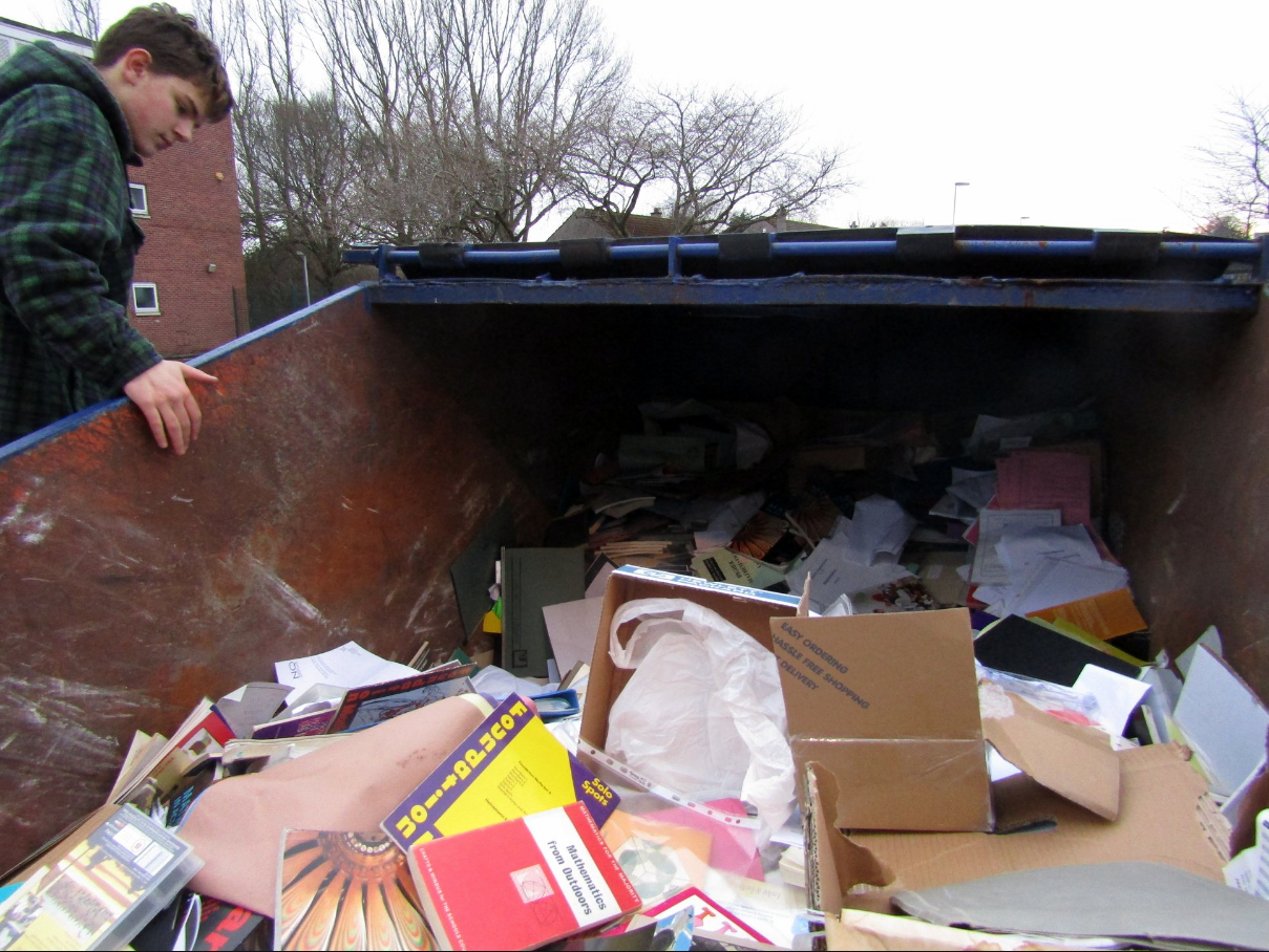 A volunteer sifts through the skip at the old school, with text books clearly visible.