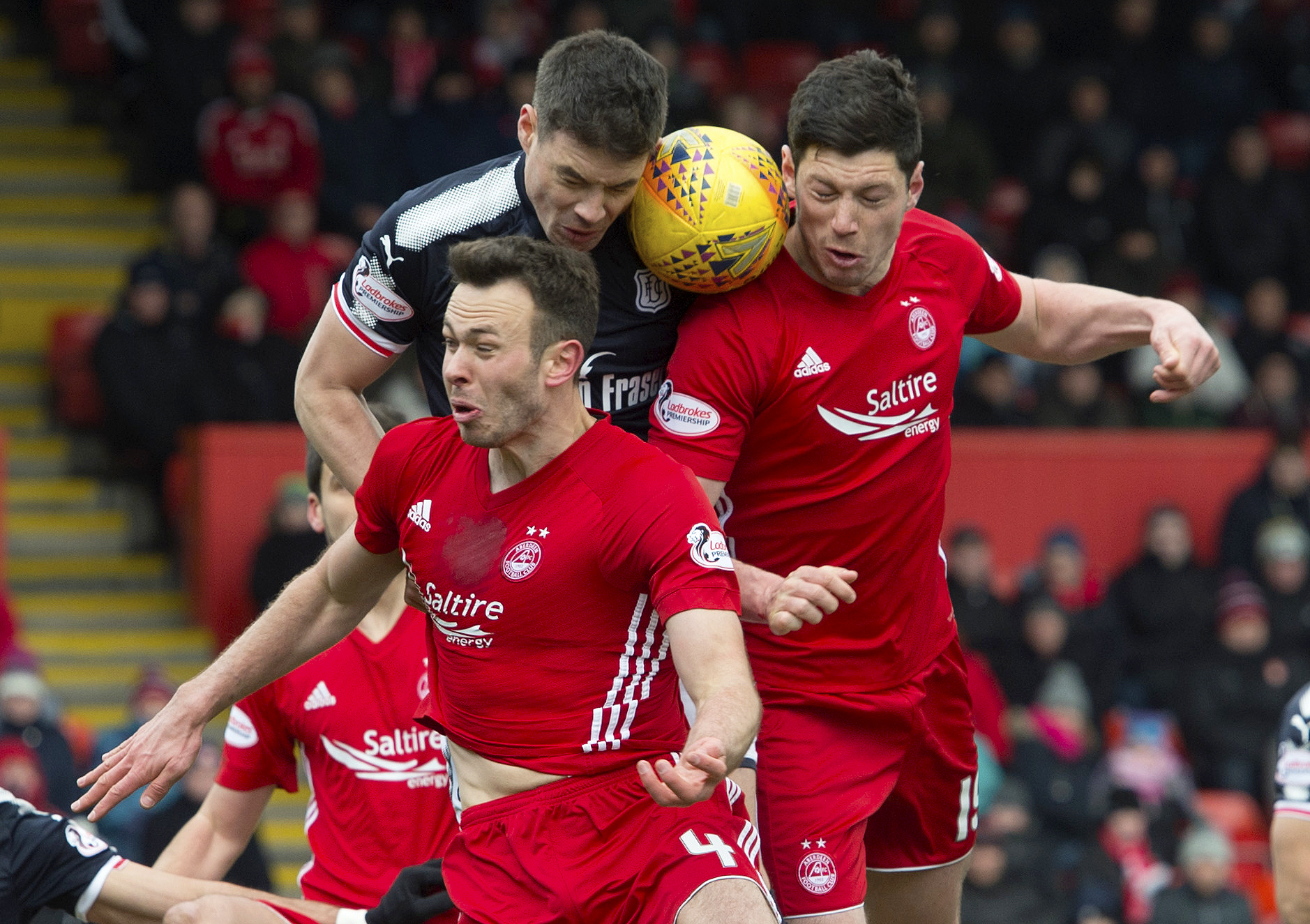 Darren O'Dea battles in the air with two Aberdeen men.