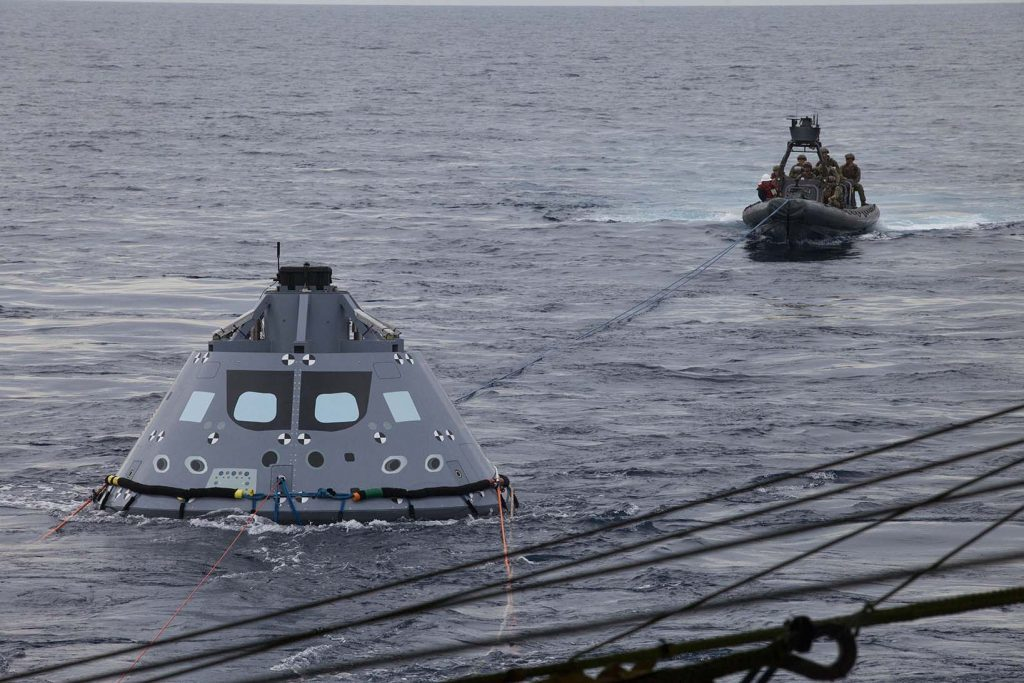 U.S. Navy divers and other personnel in a rigid hull Zodiac boat attach tether lines to a test version of the Orion crew module during Underway Recovery Test 5 in the Pacific Ocean off the coast of California.