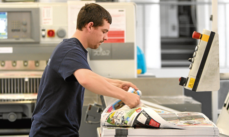 A Tradeprint technician checks print proofs.