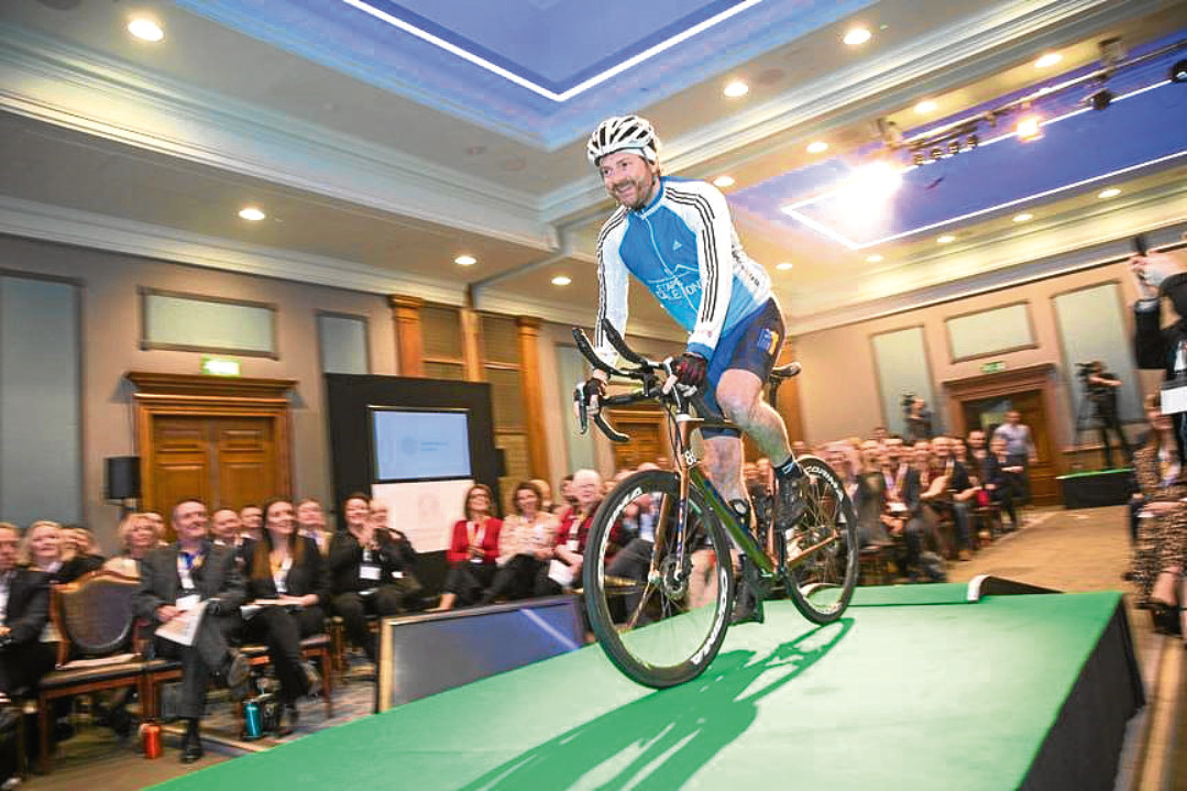 Dundee entrepreneur Chris van der Kuyl takes to the stage at the Entrepreneurial Scotland conference on Mark Beaumont's bike.