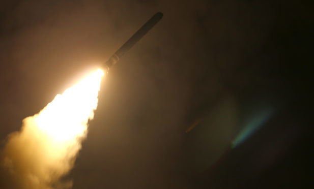 The guided-missile cruiser USS Monterey (CG 61) fires a Tomahawk land attack missile at Syria on April 13.