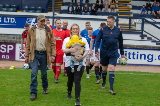 Ryan's partner Clare carrying son Hadden onto the pitch.