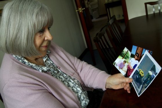 Patsy Kilbride looking at photos of her sister Janet Cameron.