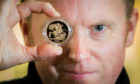 A collection of gold sovereign coins are expected to fetch large sums of money from upcoming auction. Picture shows 'Goldeneye' Nick Burns (auctioneer) with one of the coins.