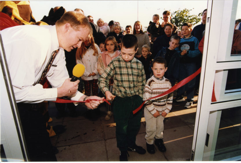 Colin Ford, grandson of the winner of the competition to open the Toys 'R' Us store in Dundee (Mrs Jane Ford) cuts the ribbon at the store on Saturday watched by brother Bryan, and manager Simon Tilley in 1996.