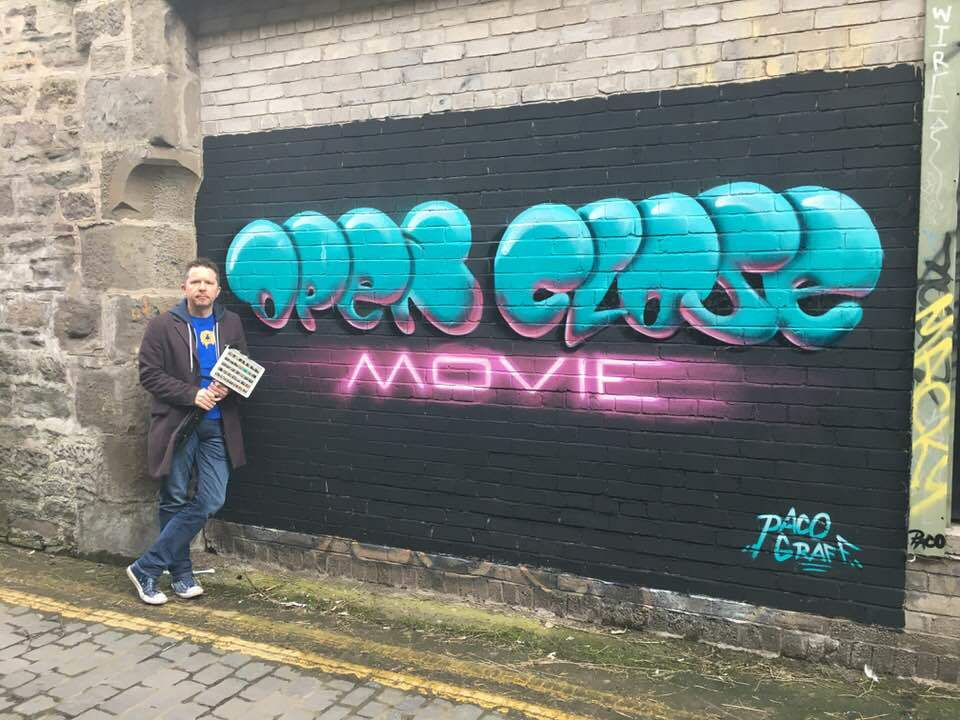Jon Gill with a mural depicting the logo for his documentary, painted in an alleyway near the Dundee bus station.