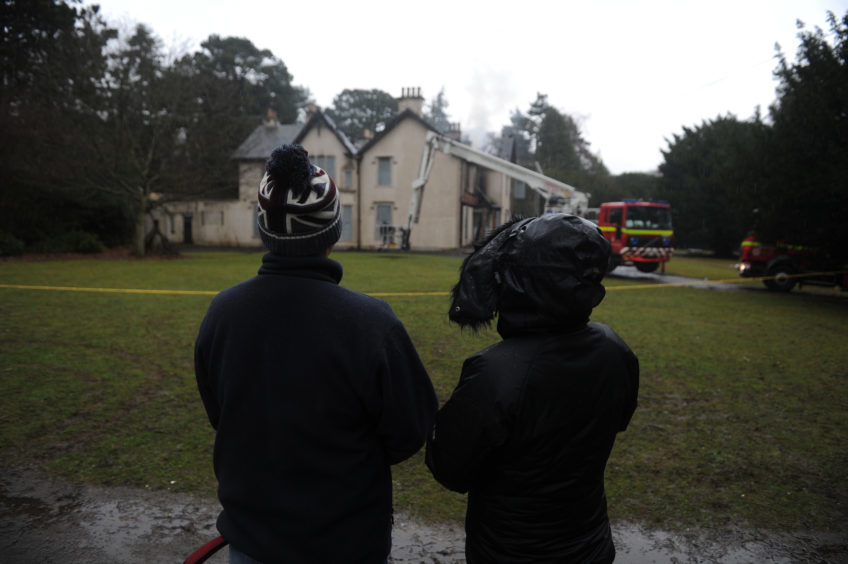 Locals watch on as frefighters keep a close eye on the scene and damp down the remnants of the roof fire.