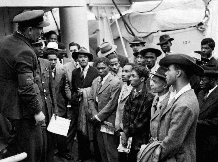 """Jamaican immigrants with RAF officials from the Colonial Office after the ex-troopship HMT """"Empire Windrush"""" landed them at Tilbury in Essex in 1948."""