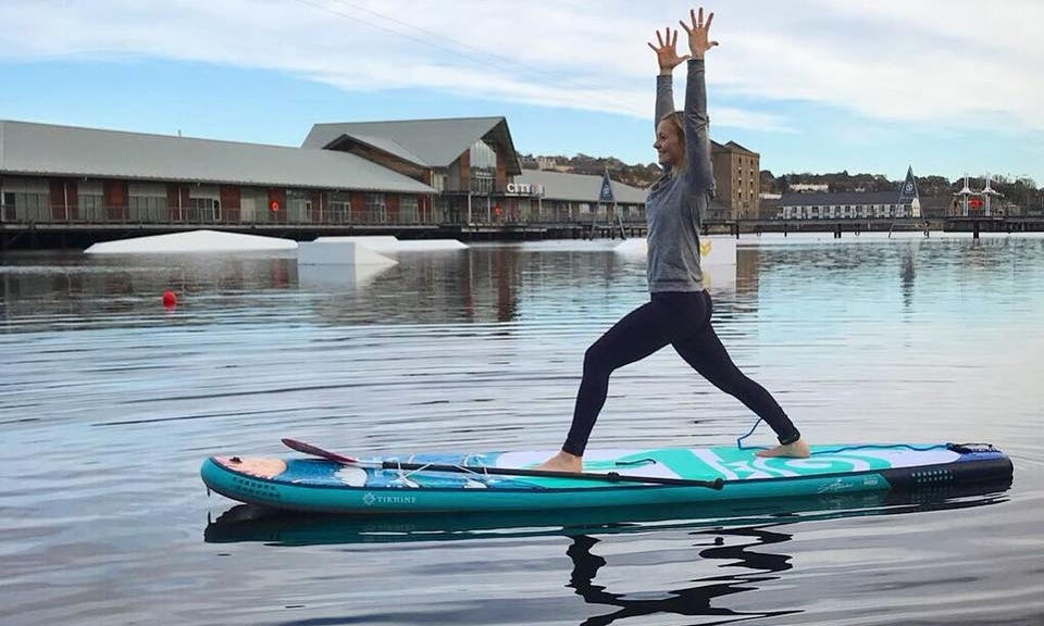 Instructor Michaella demonstrating a yoga pose on a paddle board at City Quay.