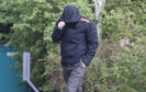 Stuart Grant hides from the camera as he arrives at court over possession of indecent images.