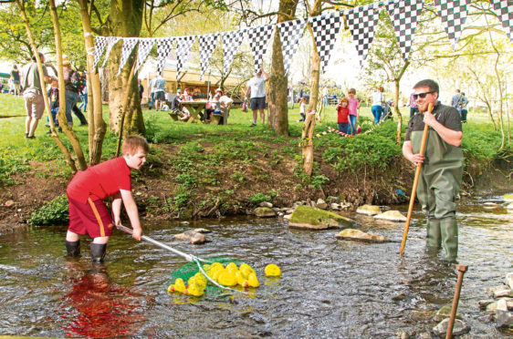 Five year old volunteer Brandon Davidson helping collect the ducks at the finishing line supervised by community outreach ranger Ross Hughes