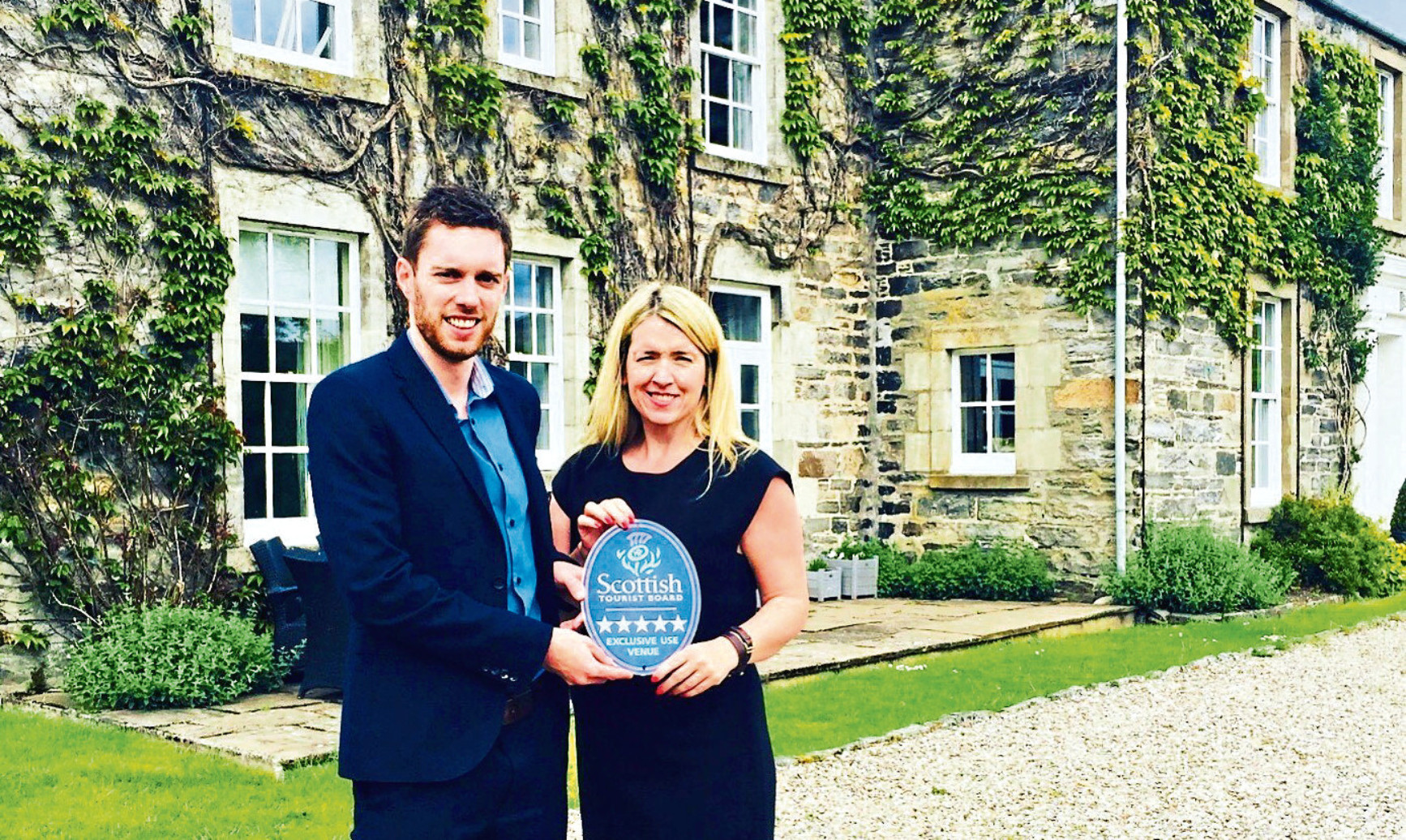 Anne MacDonald receives the Old Manses ratings plaque from Neil Christison of Visit Scotland