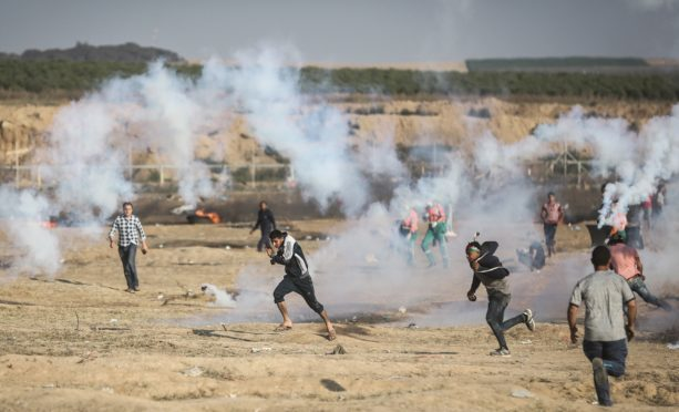 Palestinian protesters run from tear gas canisters fired by Israeli security forces in Gaza City.