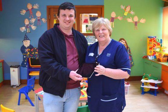 Menzieshill resident Arthur Hayburn donates an iPad to senior charge nurse Catherine Borland