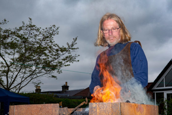 Blacksmith Jim Shears at his forge showing visitors how to manage metal