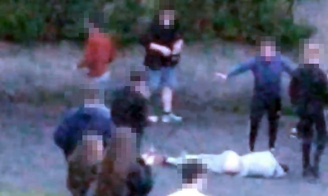 A figure lies hurt on the ground as one youth (second from right) steps in to stop the attack.