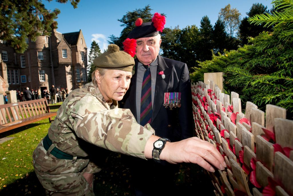 Major (retired) Ronnie Proctor watches as 2LT Sharon Swash (Black Watch AFC - Perth Viewlands) places a cross on the wall to mark the 100th anniversary of the Battle of Loos