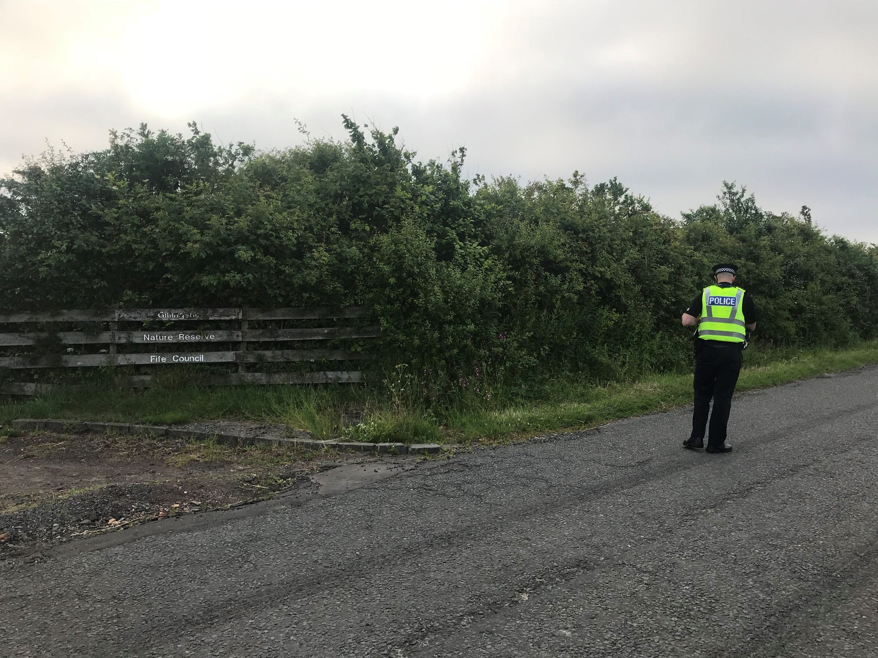 A police officer maintains a cordon outside the reservoir