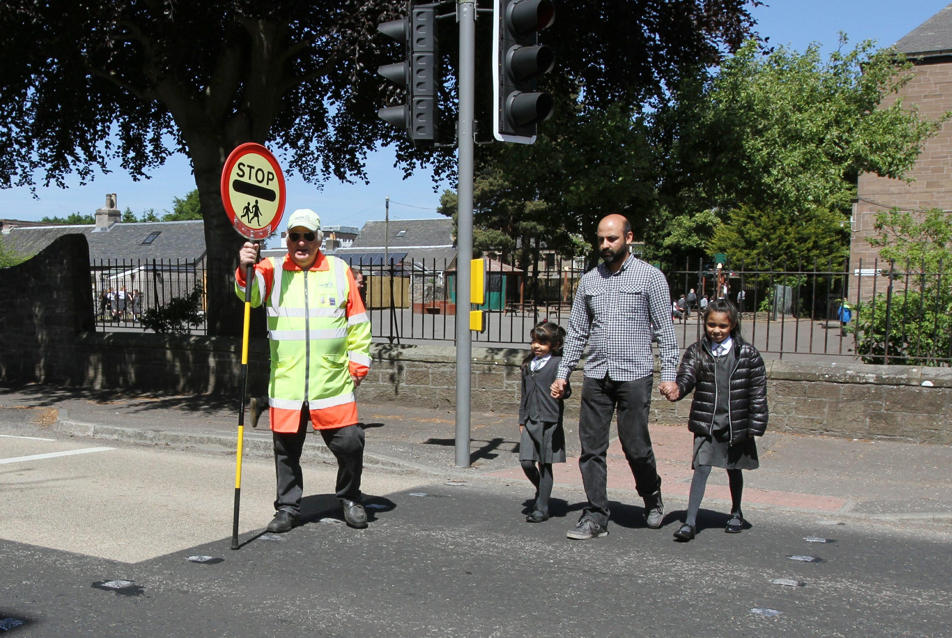 Ian Loney (70) helps Tasib Hussain and his daughters Ashlina (9) & Suhana (5) across  busy road