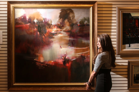 Kate Cunningham, gallery assistant and artist with a painting by Oscar Goodall RSW, entitled Weir and River.