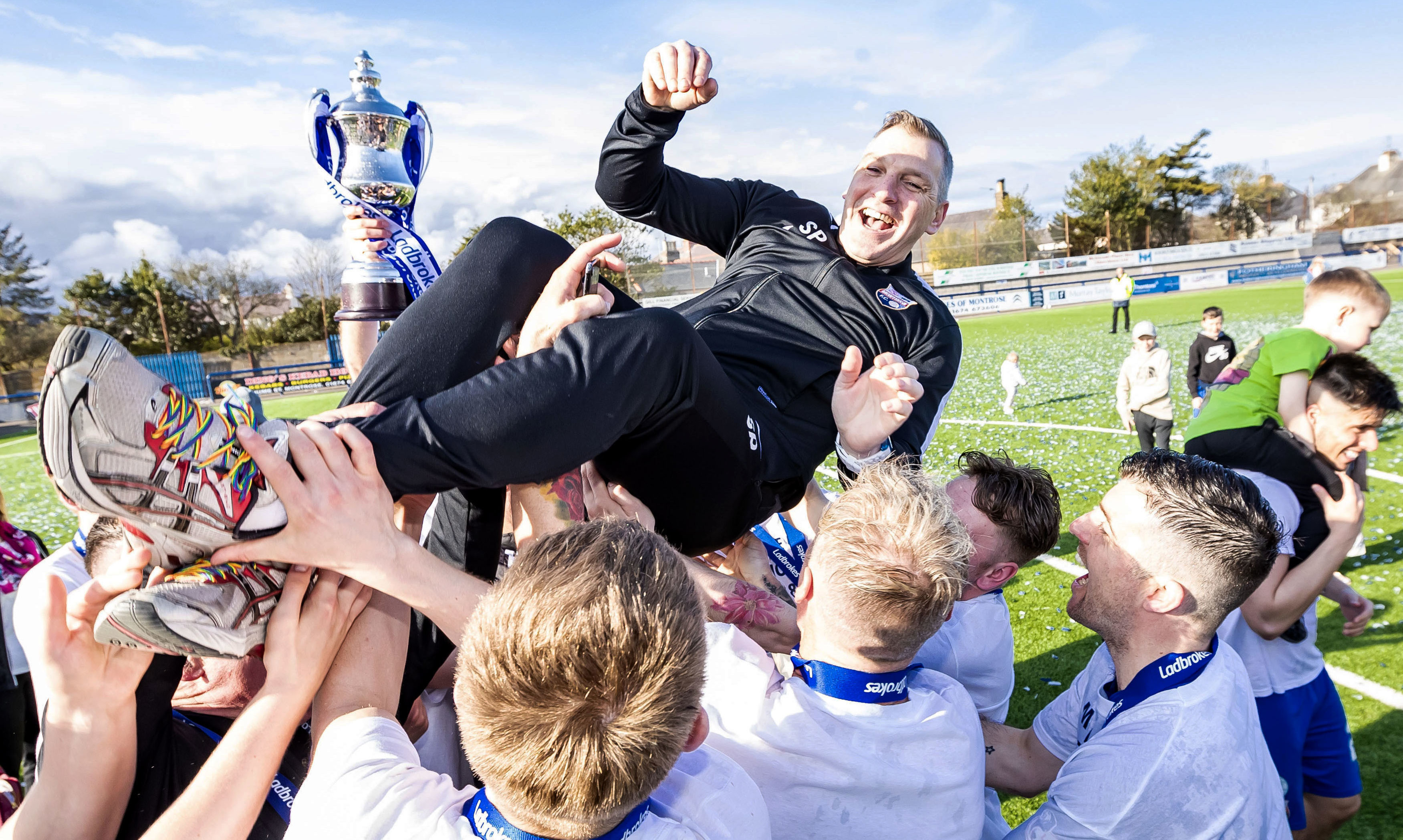 The Montrose players celebrate with boss Stewart Petrie after clinching League 2 ttile.