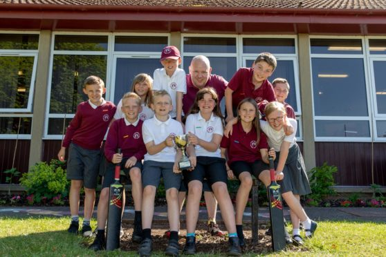 Cricket coach Alan Surtees (centre) with his winning P6 team.