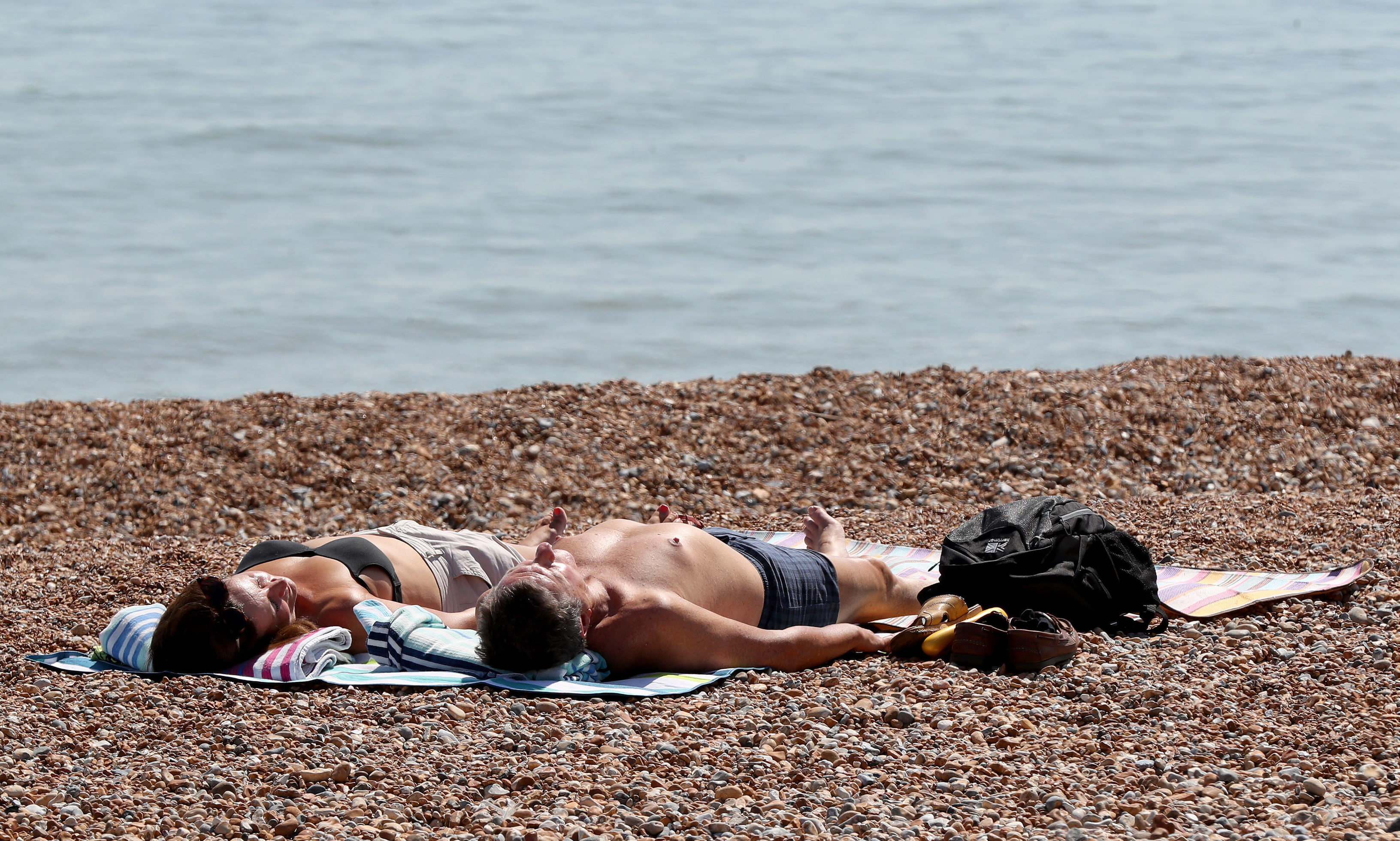 A couple relax in the sunshine on the beach at the start of the June heatwave in 2018.