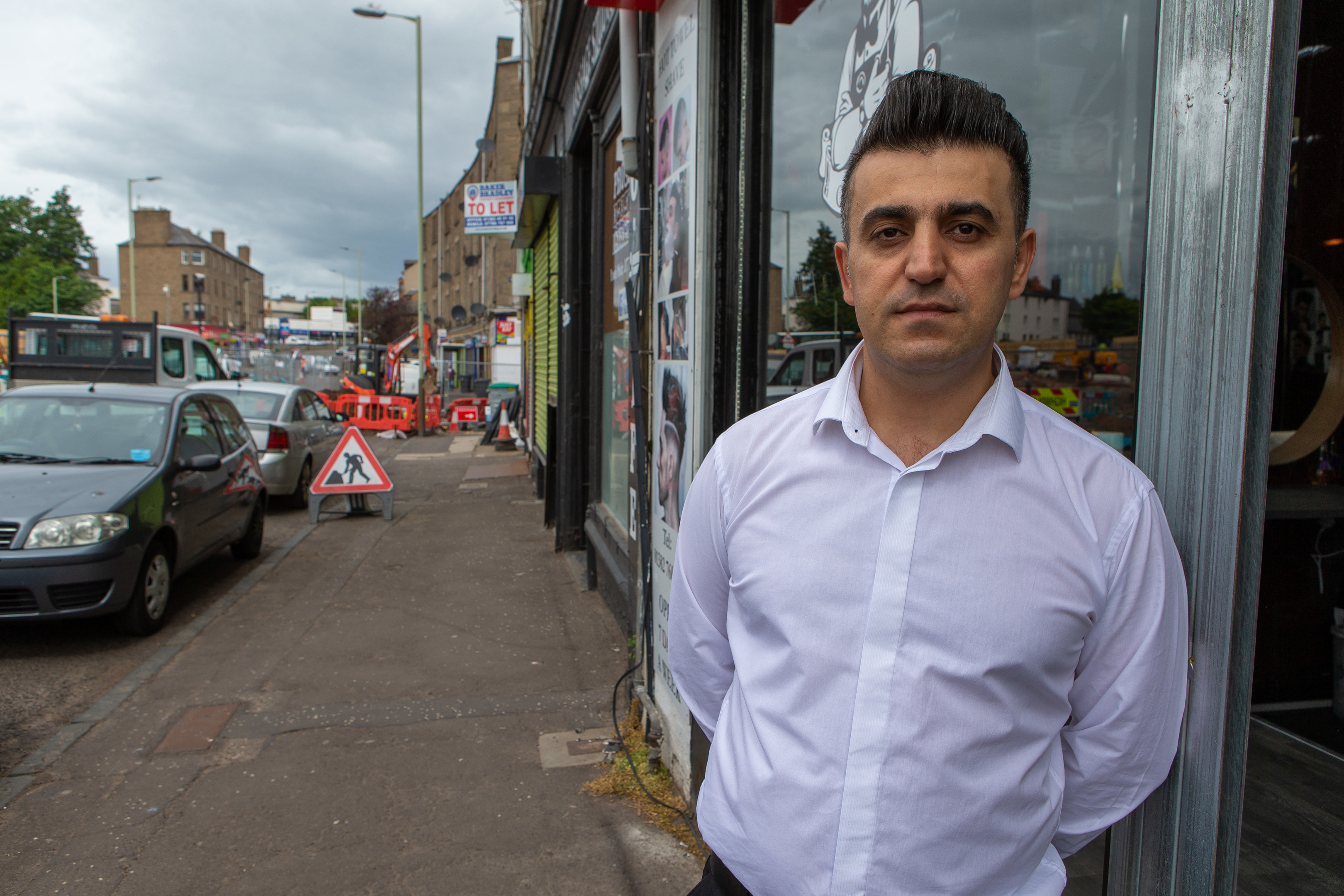 Yousif outside his barber's shop on Strathmartine Road.