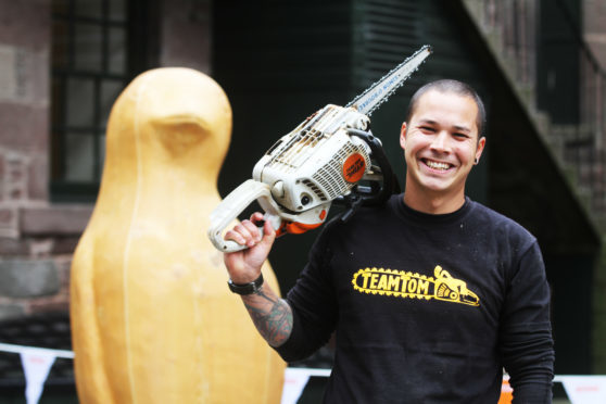 Chainsaw artist Tom Harris-Ward with the sculpture he created for the Maggie's Penguin Parade.